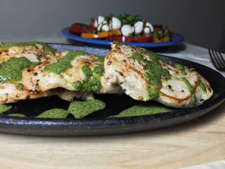 Chicken Paillard with three-herb summer sauce in the foreground, and caprese salad in the background.