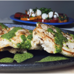 Chicken paillard with three-herb sauce on a hot plate with caprese salad in the background