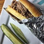 Slow Cooker Italian Roast Beef on a roll with refrigerator dill pickles on the side.