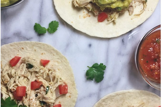 Cilantro Lime Slow-cooker Chicken Tacos topped with tomatoes, guacamole, sour cream and cilantro