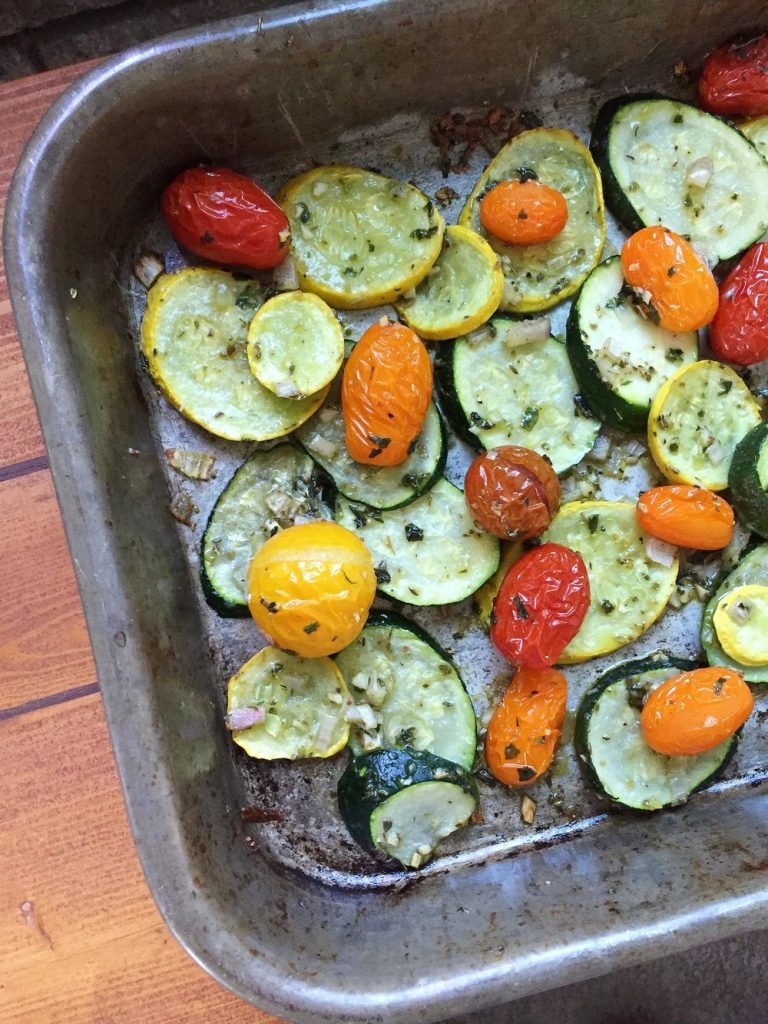 Roasted squash and zucchini with tomatoes on a sheet pan