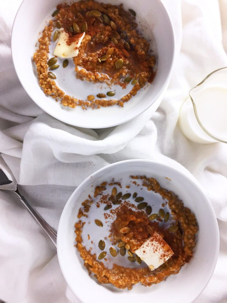Two white bowls of pumpkin spice steel cut oatmeal with milk, butter, cinnamon and pepitas beside a milk cup and a spoon, on a white cloth napkin.