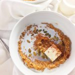 A white bowl of pumpkin spice steel cut oatmeal with milk, butter, cinnamon and pepitas on a white cloth napkin