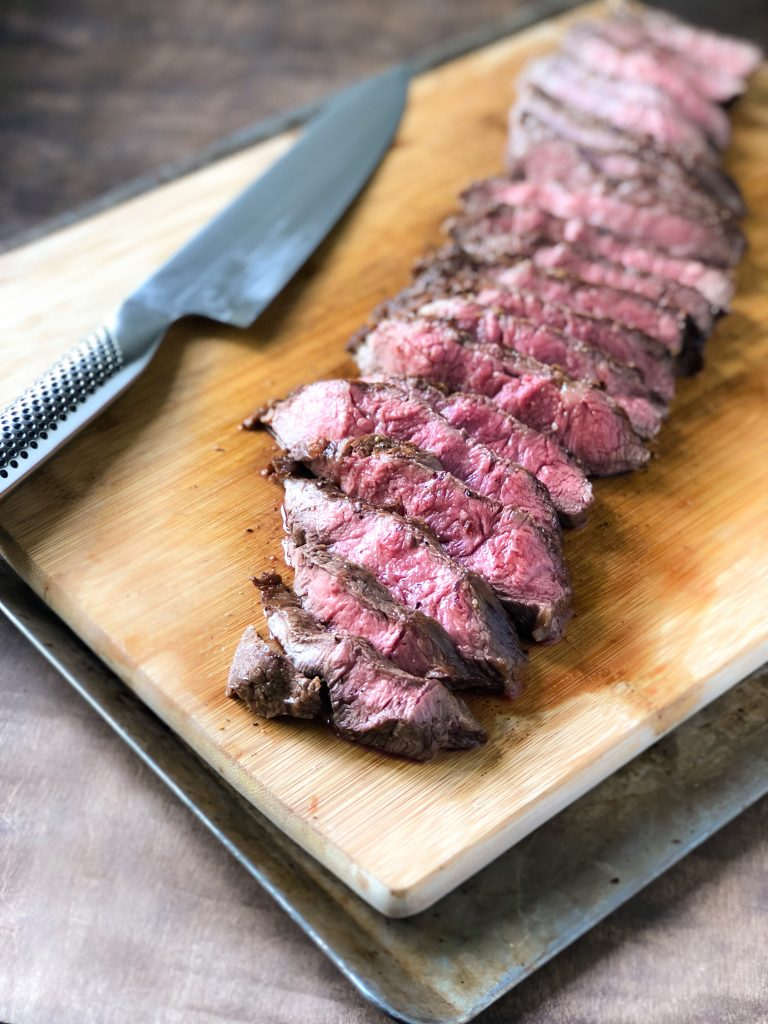 Flat iron steak sliced on a cutting board next to a chef's knife.