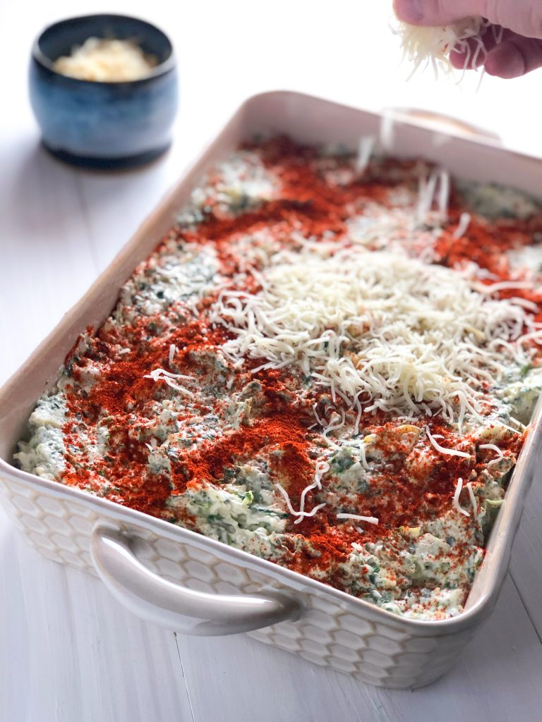A dish of unbaked Ultimate Spinach Artichoke dip with a hand sprinkling Italian blend cheese on top.