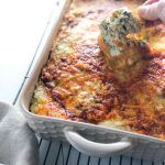 Ultimate Spinach Artichoke dip in a baking dish with crostini being dipped into it.