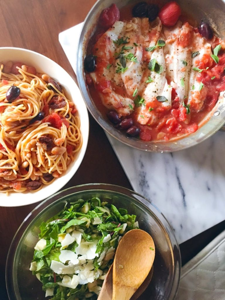 An overhead view of Whitefish in Tomato Sauce with Olives, Bucatini with Tomatoes, Olives and White Beans, and a salad with shaved parmesan