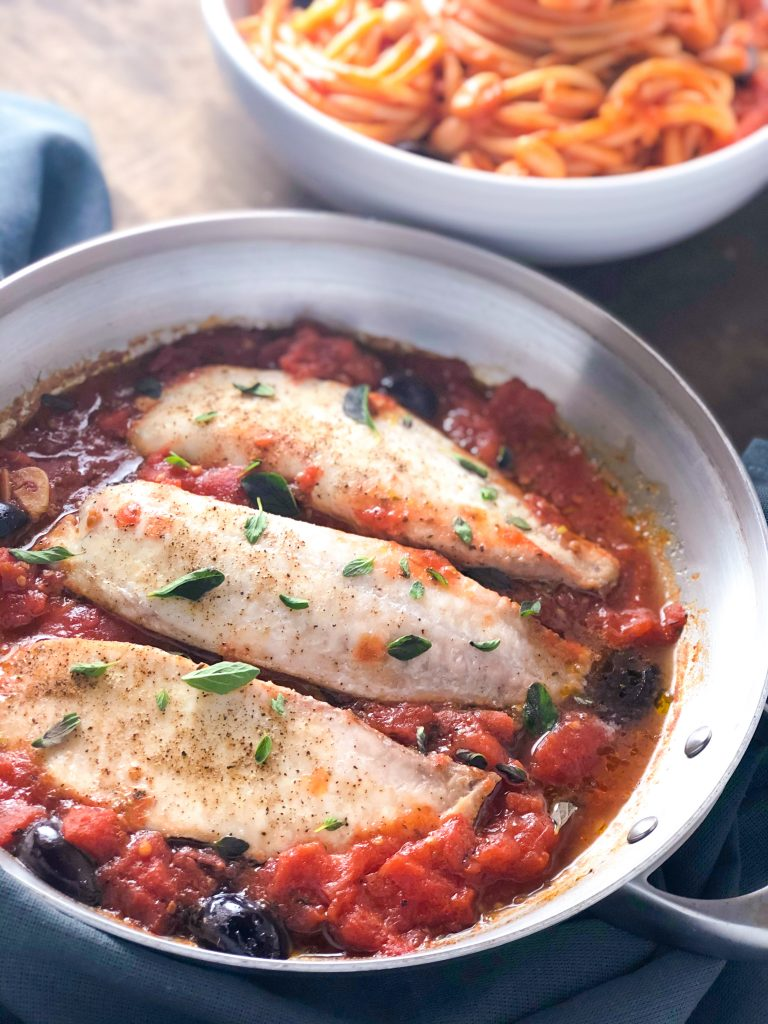 A pan of Whitefish in Tomato Sauce with Olives with a bowl of pasta in the background