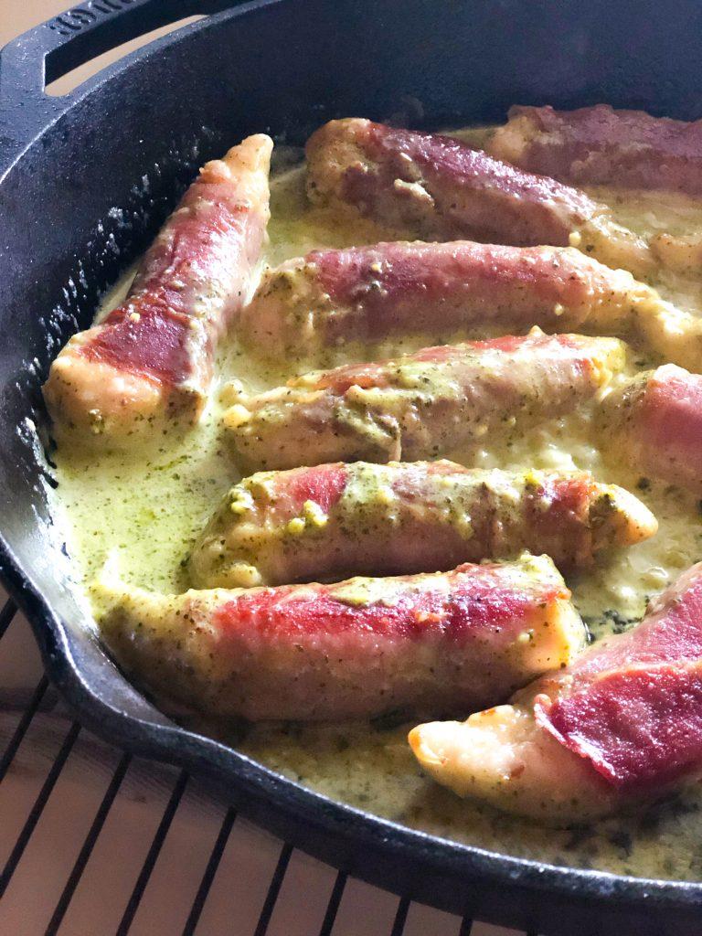 Prosciutto-wrapped Chicken with Pesto Cream Sauce in a cast-iron skillet