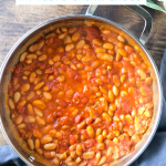 A pan of fagioli all'uccelletto (Tuscan Braised Beans) on a gray towel with sage, with a graphic naming the food for Pinterest