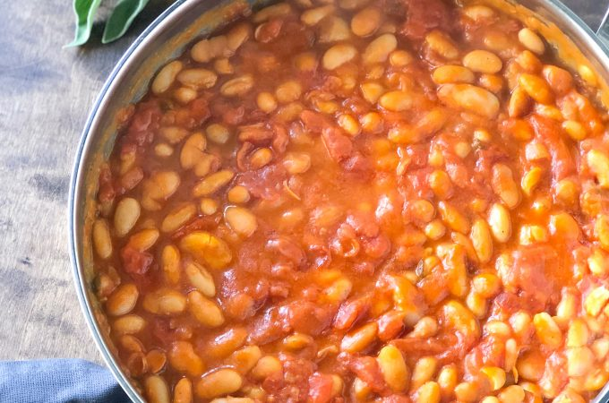 Fagioli all'uccelletto (Tuscan Braised Beans) in a pan next to fresh sage leaves