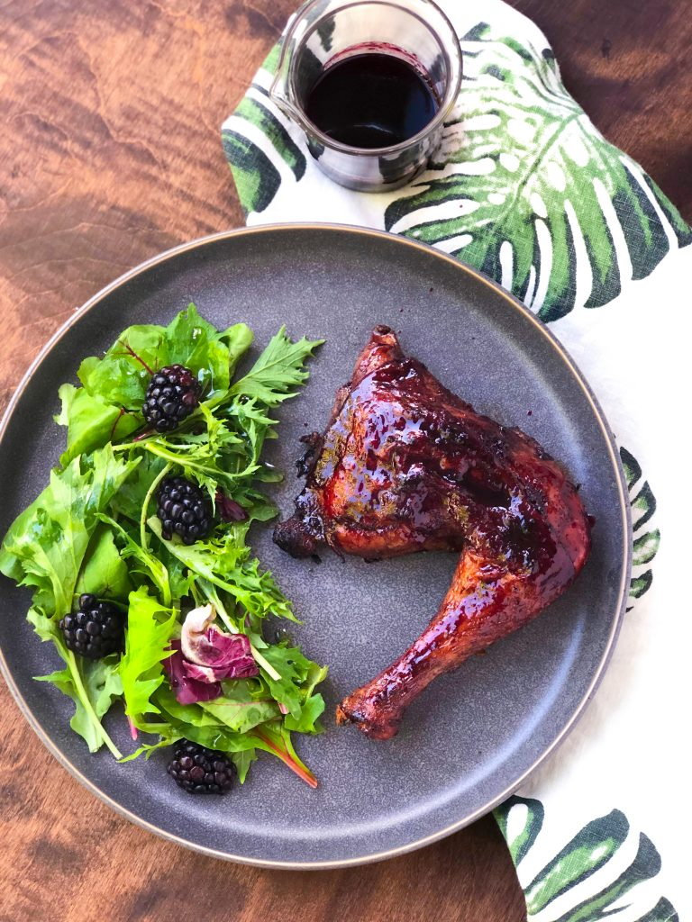 Black Raspberry Glazed Chicken Legs with blackberry salad and a glass with more glaze on a gray plate, on a white tea towel with green leaves.