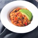Cheesy Vegetarian Quinoa Enchilada Bake in a white bowl topped with avocados.