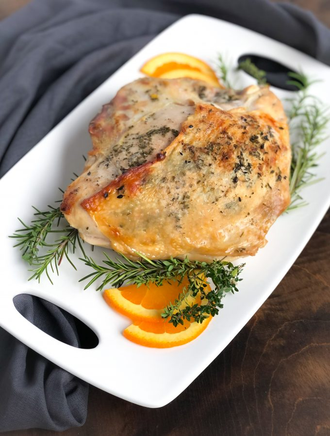 Roasted turkey on a white platter with orange slices, rosemary and thyme.