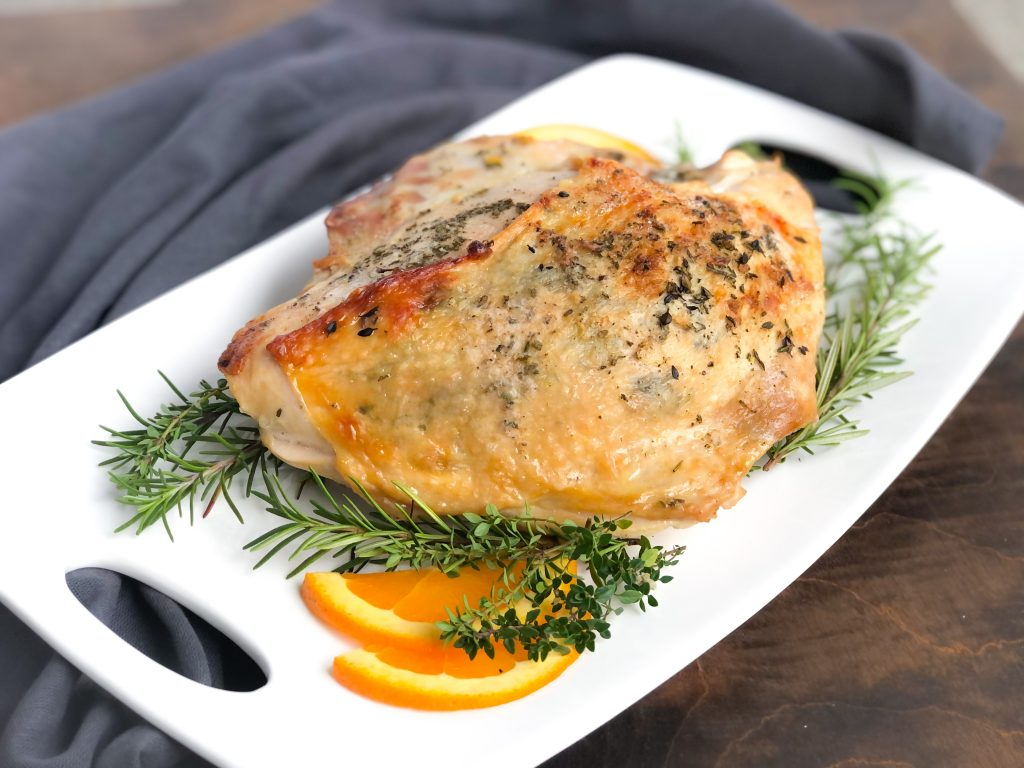 Horizontal photo of roasted turkey on a white platter with orange slices, rosemary and thyme.