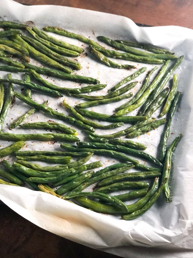 Roasted green beans on a baking sheet with parchment paper