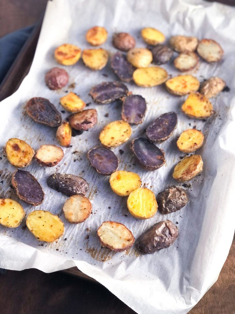 Roasted Tricolor Fingerling Potatoes on a sheet pan with parchment paper